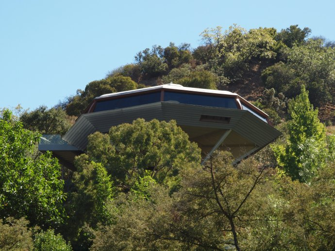 The Chemosphere, a distinctive octagonal house that stands on a 30-foot pole, peeks above the treetops.  This abode was designed by the architect John Lautner in 1960.