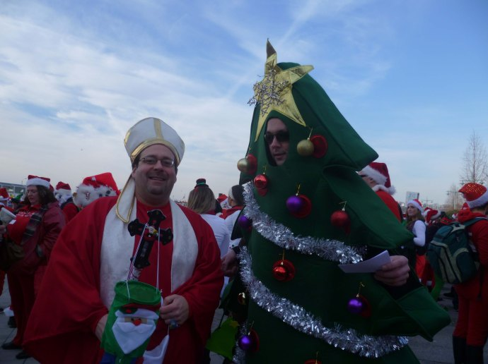 A cardinal palling around with a Christmas tree is no odder than many of the other scenes that take place at Santacon.