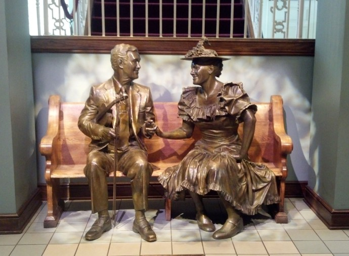 The statues of Roy Acuff and Minnie Pearl seated in the lobby of Ryman Auditorium.
