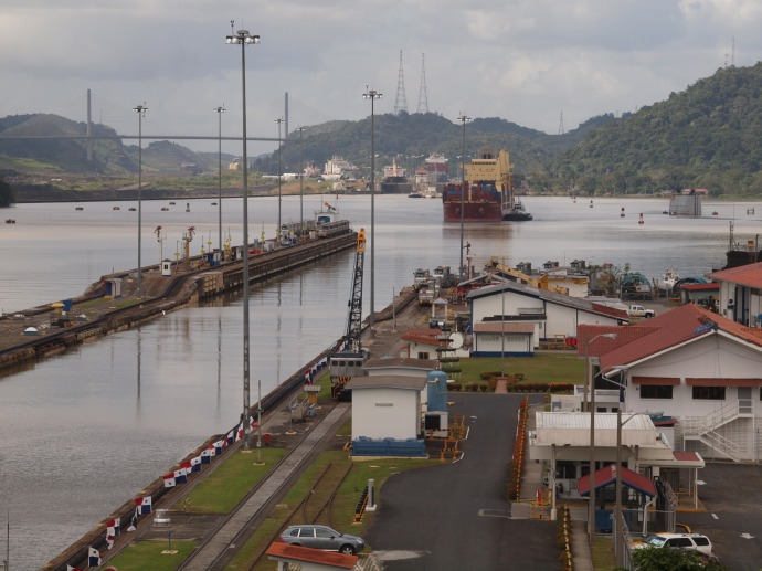 As viewed from the visitor's center, an eastbound container ship approaches the Miraflores locks.