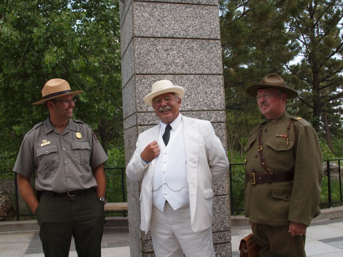 Two Teddy Roosevelts, side-by-side, on the grounds of Rushmore. The very different outfits represent two distinct phases of TR's career.