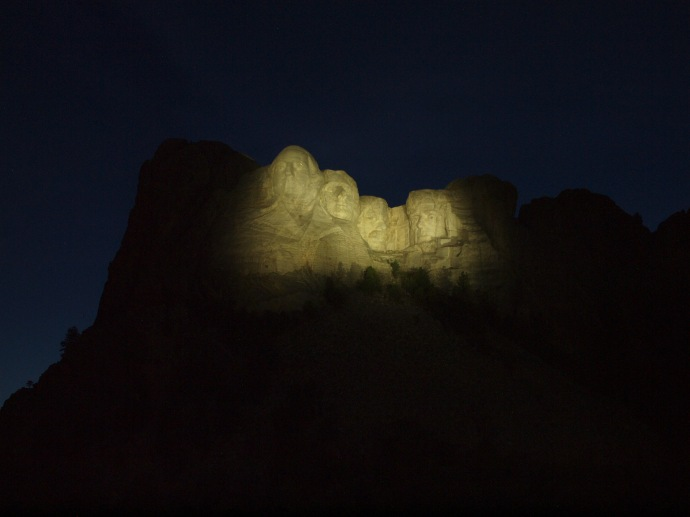 The faces of Mount Rushmore, illuminated at dusk.