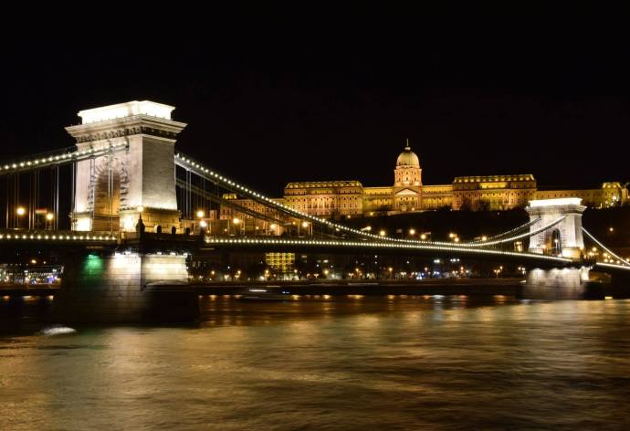 A view of the Chain Bridge at night, with Buda Castle looming in the background.